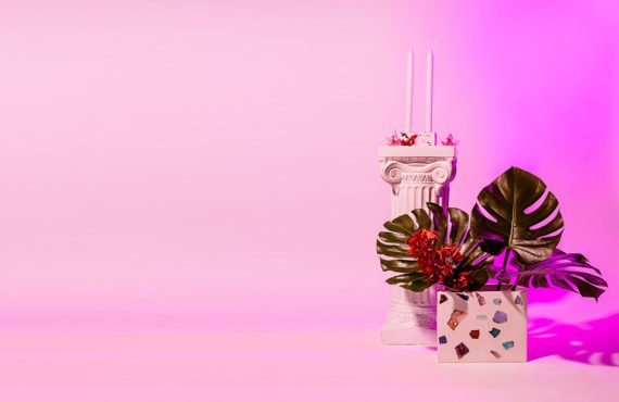 A pink terrazzo design vase with leaves and styled in a purple light.